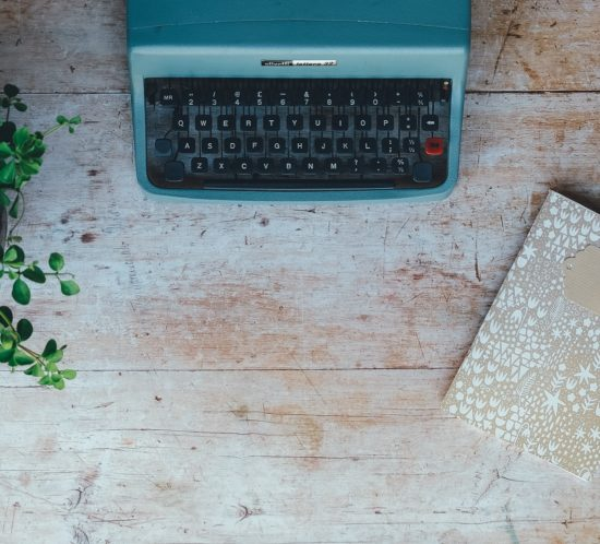 turquoise typewriter on rustic desk in-between plant and notebook